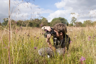 Boy taking photograph in meadow