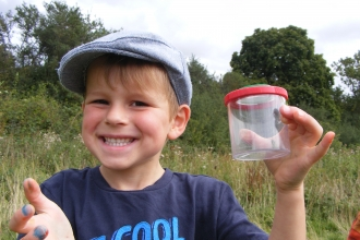 young child holding up a specimen at a wildlife explorers event at Sutton Courtenay Environmental Education Centre.