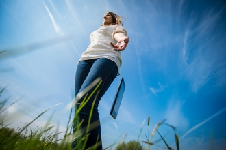 Woman throwing phone onto the grass