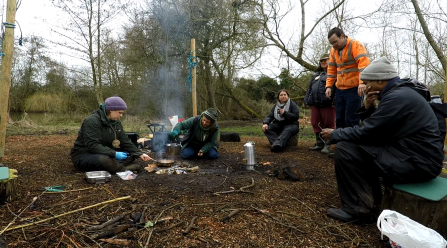 Engaging with Nature participants cooking around a fire